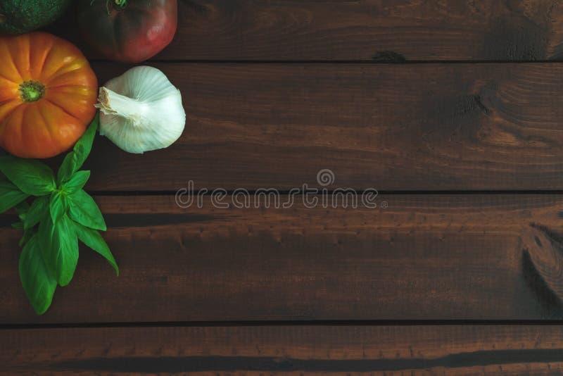 Tomates, ail, avocat et basilic d'héritage sur un conseil brun photo stock