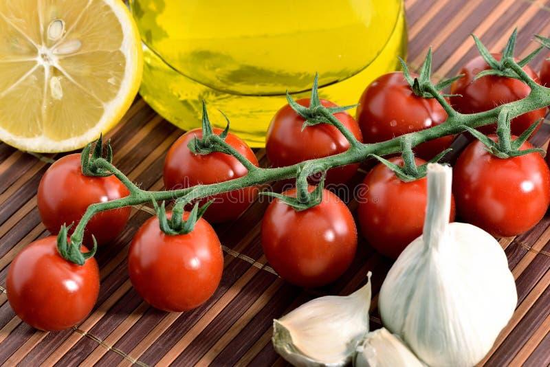Tomates, ajo, limón, tomates y aceite imagenes de archivo