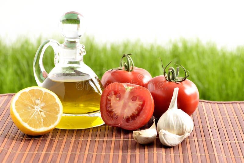 Tomates, ajo, limón, tomates y aceite foto de archivo