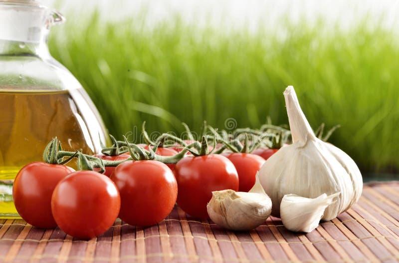 Tomates, ajo, tomates y aceite imagenes de archivo