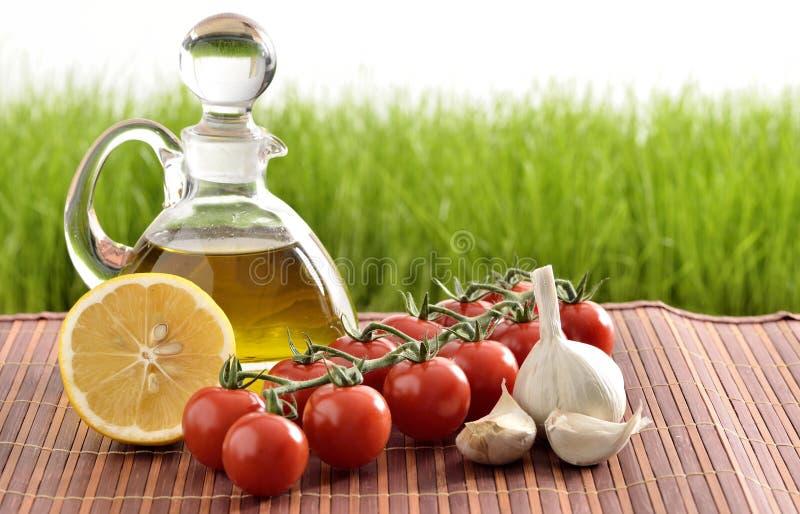Tomates, ajo, tomates y aceite imagen de archivo