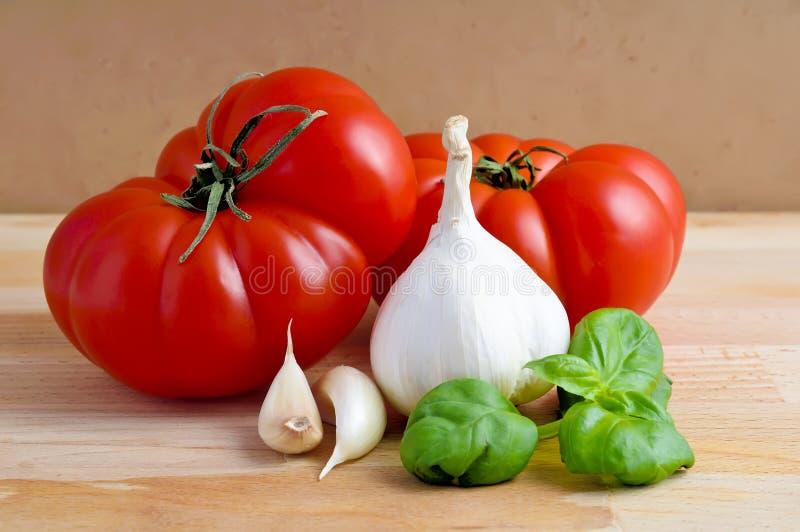 Tomates, ajo y albahaca imagen de archivo