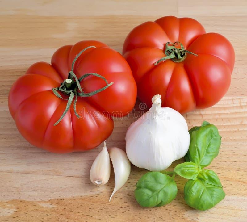 Tomates, ajo y albahaca imágenes de archivo libres de regalías