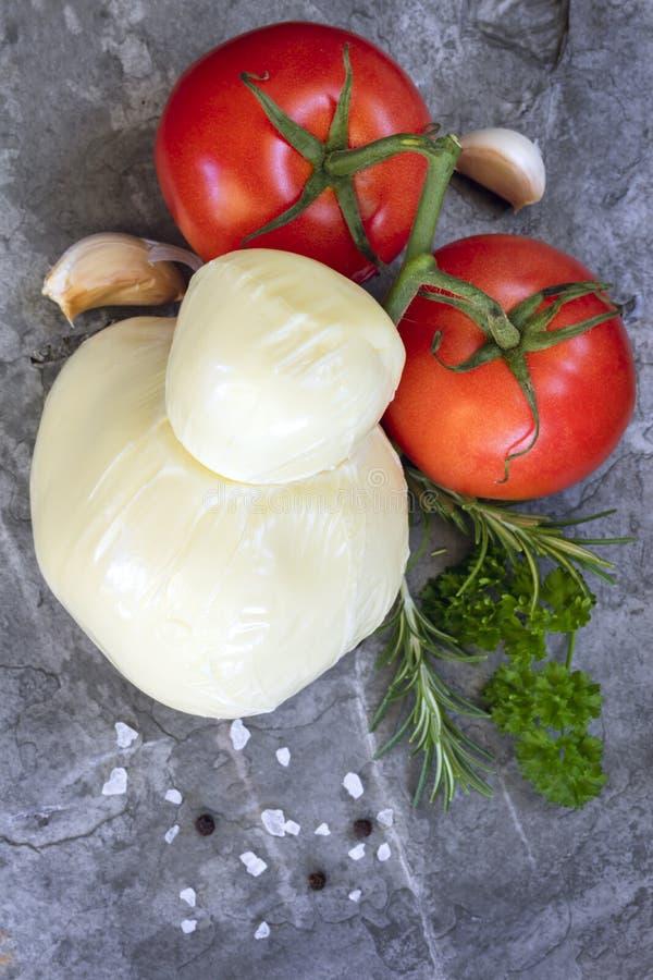 Tomates alho da mussarela do fundo do alimento e opinião superior das ervas fotografia de stock
