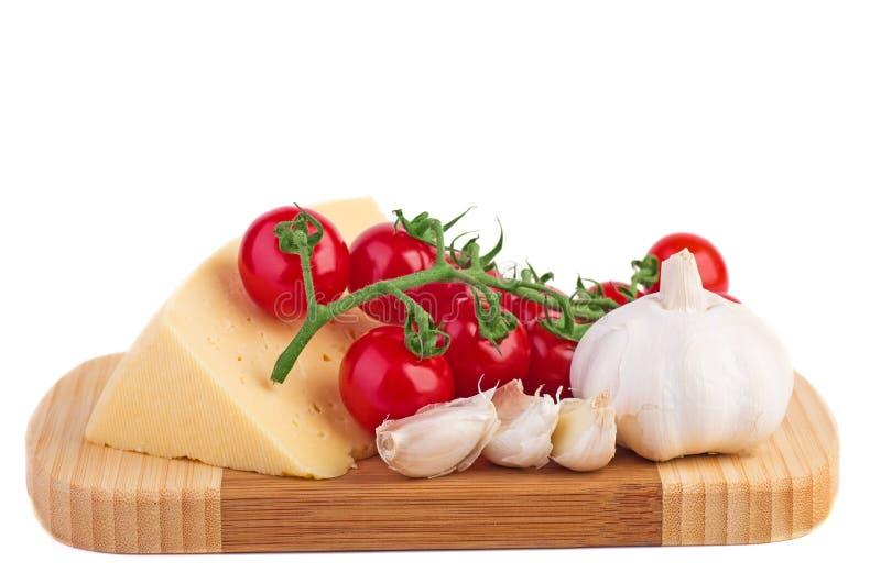 Tomates, alho e queijo em uma placa de corte de madeira fotografia de stock royalty free