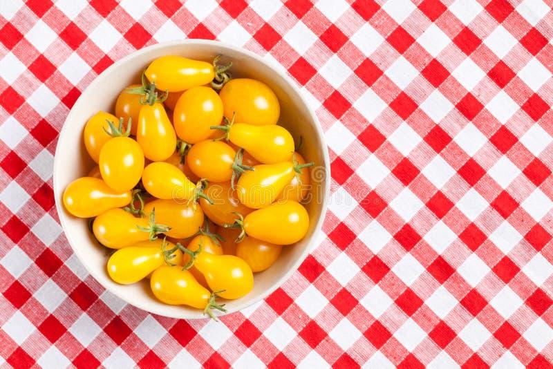 Tomates amarelos no tablecloth do piquenique fotos de stock