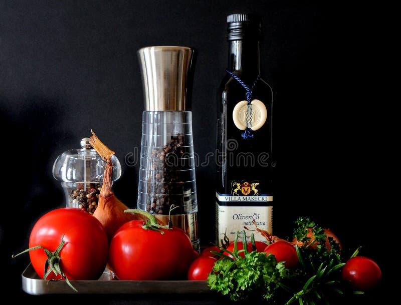 Tomates ao lado dos abanadores e da Olive Oil Bottle fotos de stock royalty free
