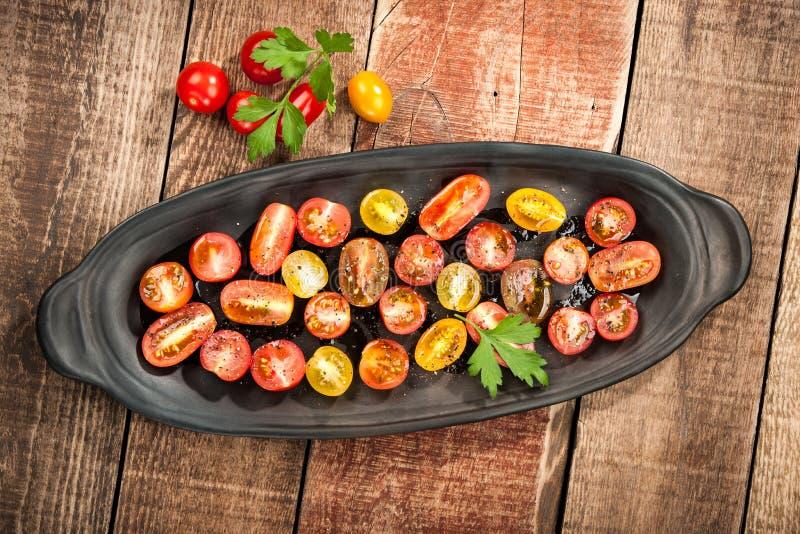Tomates-cerises colorées coupées en tranches avec le pétrole et l'épice photographie stock libre de droits