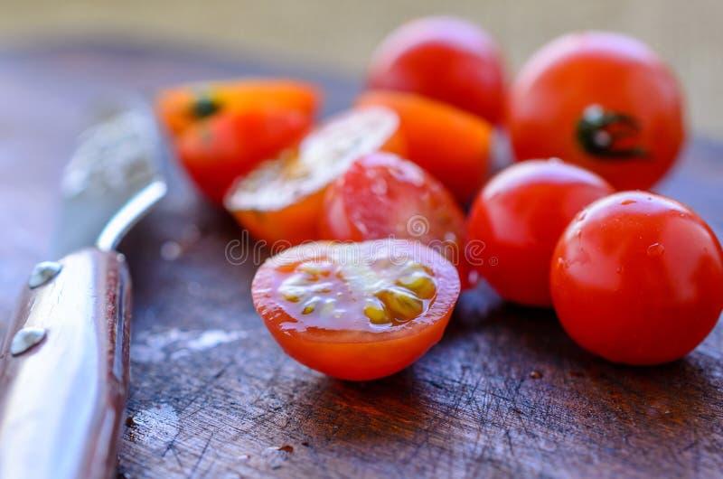 Tomates-cerises coupées en tranches et un couteau pointu avec une poignée en bois sur un fond foncé images libres de droits