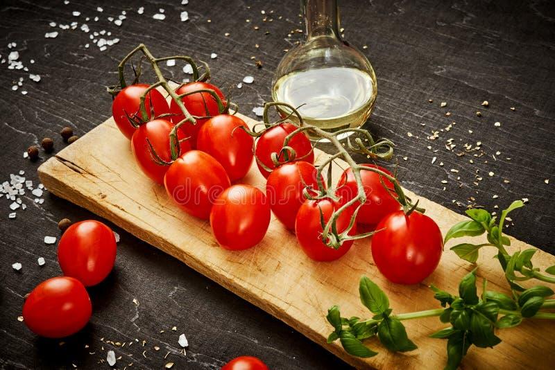 Tomates-cerises et basilic juteux sur un conseil en bois sur une table noire images stock