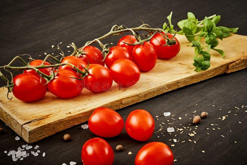 Tomates-cerises et basilic juteux sur un conseil en bois sur une table noire photographie stock