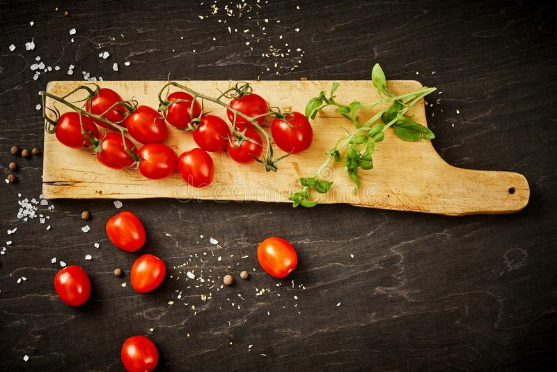 Tomates-cerises et basilic juteux sur un conseil en bois sur une table noire photos stock