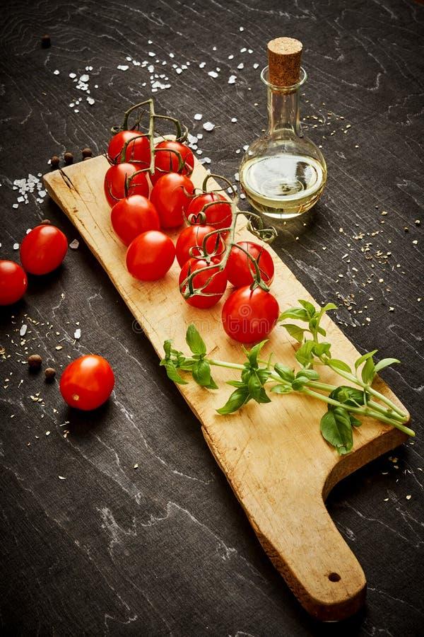 Tomates-cerises et basilic juteux sur un conseil en bois sur une table noire photos libres de droits