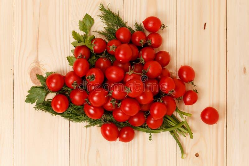 Tomates-cerises et herbes fraîches sur le fond en bois image stock