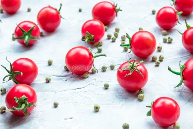 Tomates-cerises mûres dispersées sur une table concrète dispersion du poivron vert image libre de droits