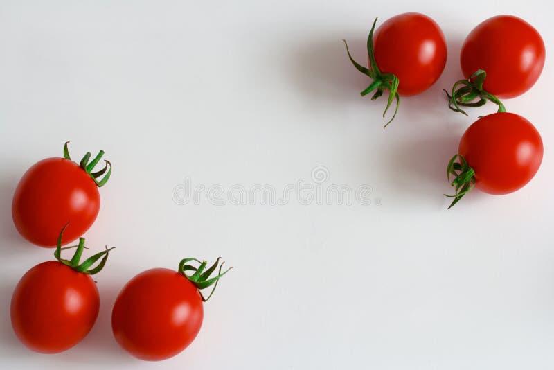 Tomates-cerises mûres rouges sur un fond blanc photographie stock libre de droits