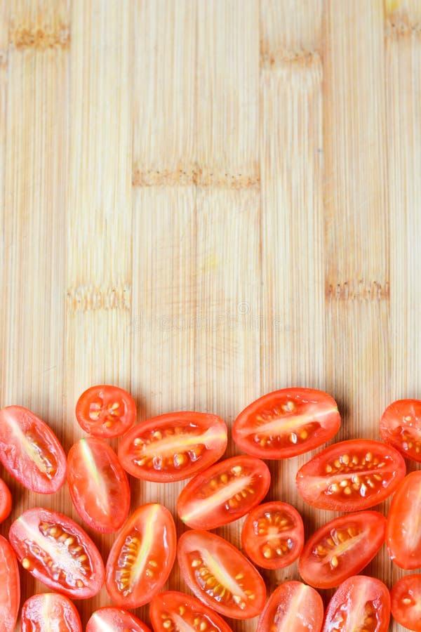 Tomates-cerises rouges coupées sur une planche à découper images stock