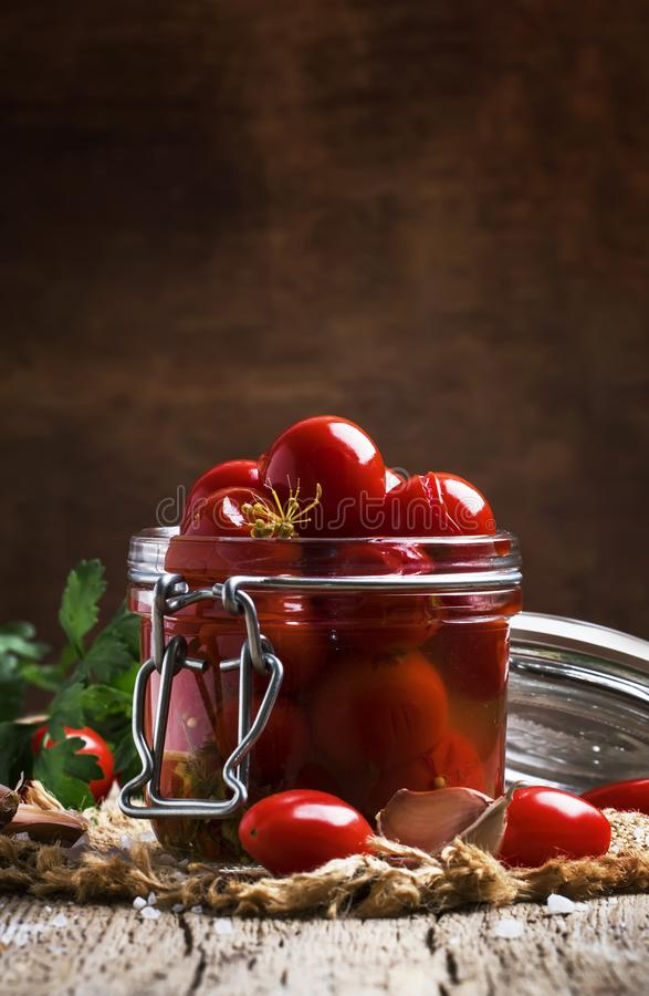 Tomates-cerises rouges marinées dans le pot en verre sur le vieux fond en bois de table de cuisine, foyer sélectif image stock