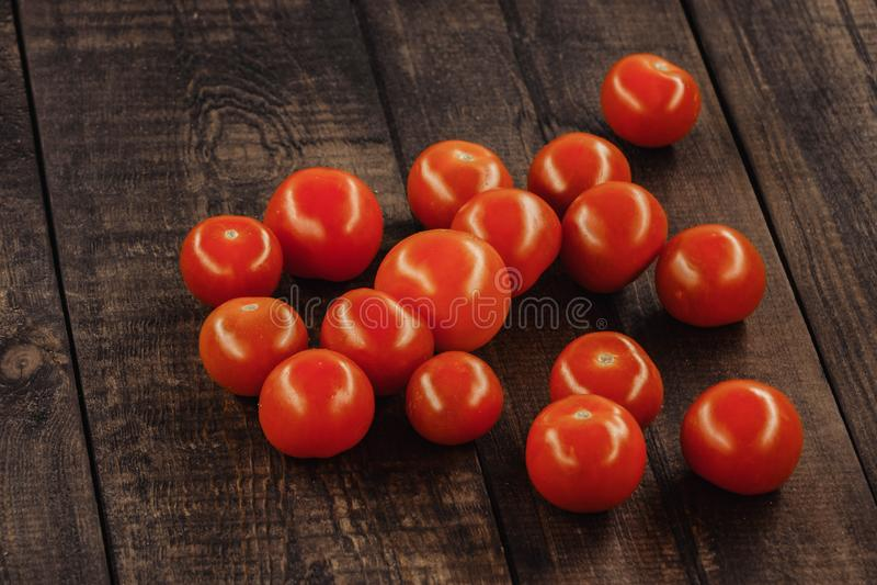 tomates-cerises savoureuses sur un support en bois, fond en bois photo libre de droits
