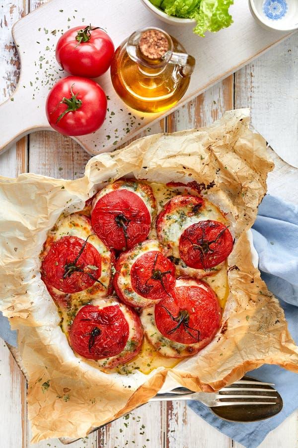 Tomates cocidos horno rellenos con espinaca, queso e hierbas foto de archivo