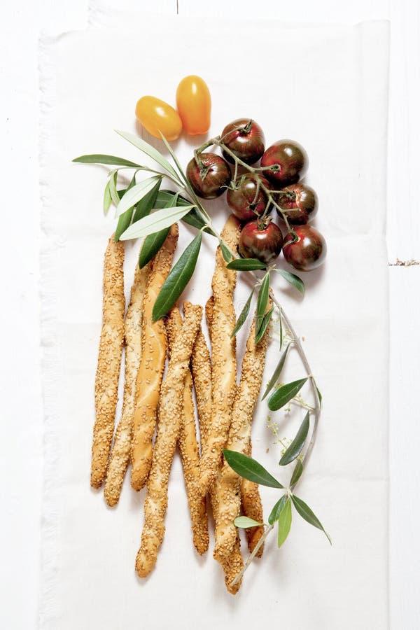 Tomates colorées, batons de pain avec les graines de sésame, huile d'olive et photo libre de droits