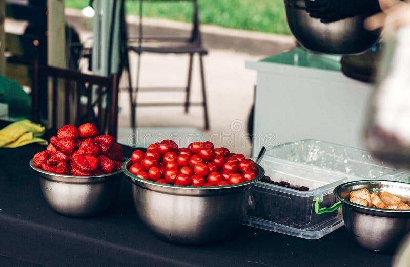 tomates colorées cerise et fraise dans des cuvettes en métal sur la table, photos libres de droits