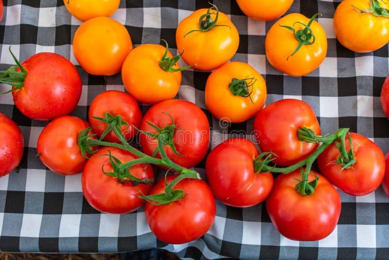 Tomates colorées sur une nappe noire et blanche photos stock