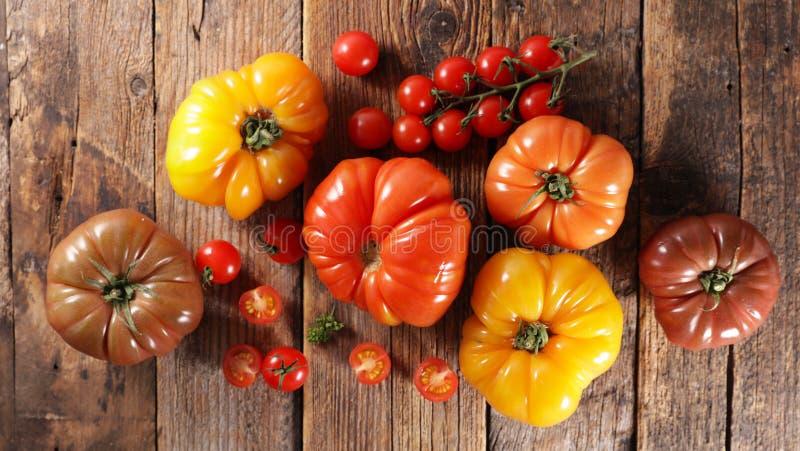 Tomates coloridos sobre fondo de madera foto de archivo