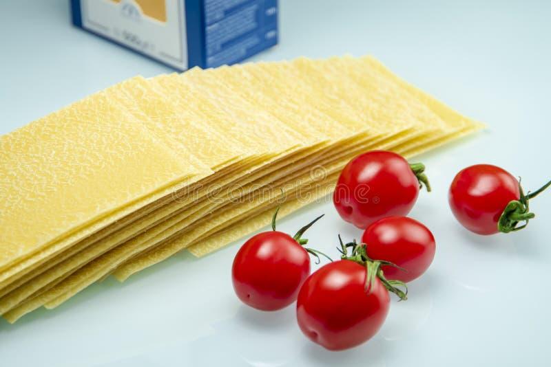Tomates com lasanhas no vidro reflexivo branco foto de stock royalty free