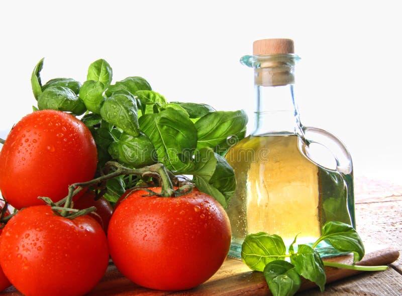 Tomates com manjericão fresca e petróleo verde-oliva imagem de stock royalty free