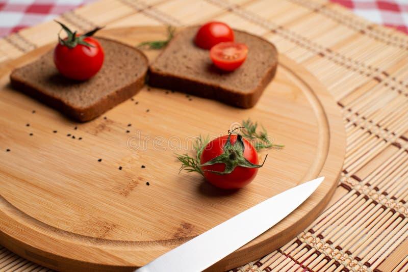 Tomates com pão preto para o almoço, pão preto com o tomate no fundo de madeira fotografia de stock