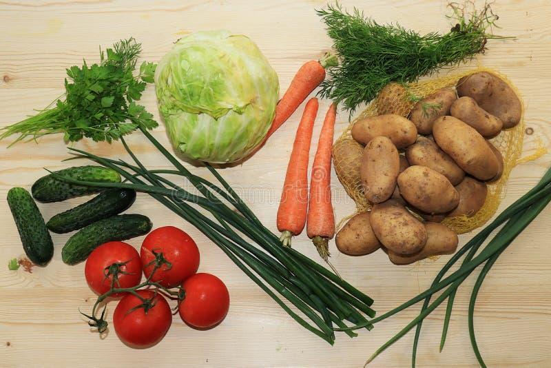 Tomates, concombres, pommes de terre, chou, verts sur un fond en bois clair, vue supérieure, le concept de la nourriture végétari photographie stock