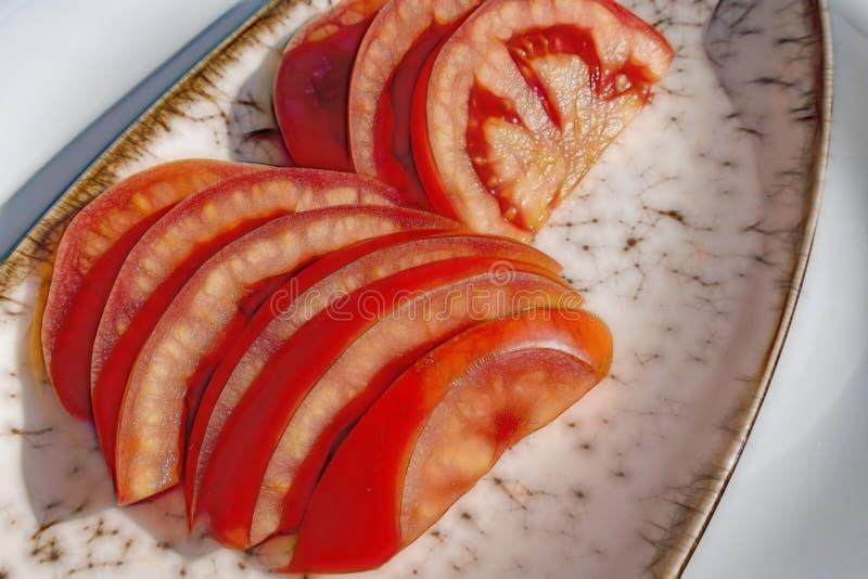 Tomates cortados preparados en placa libre illustration