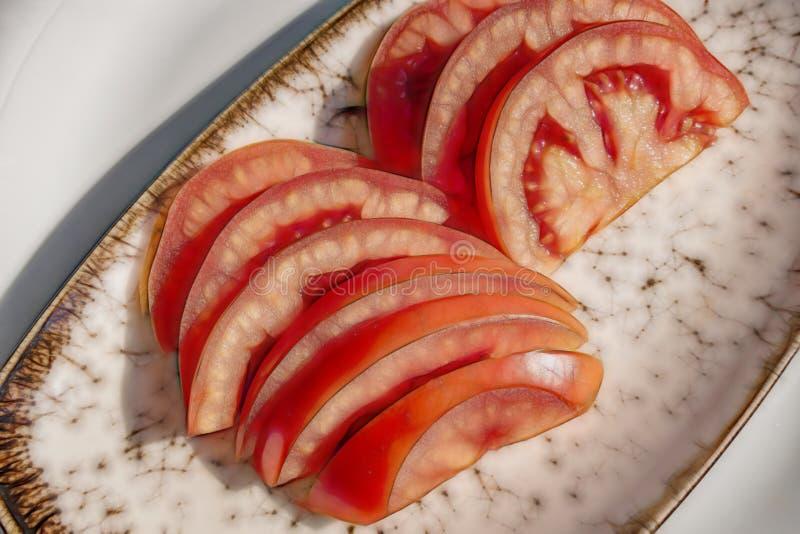 Tomates cortados prontos para comer na placa fotos de stock