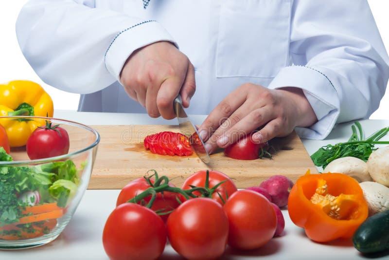 Tomates coupées par cuisinier en salade végétale photos stock