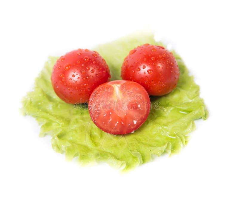 Tomates coupées se trouvant sur une feuille de salade verte photo libre de droits