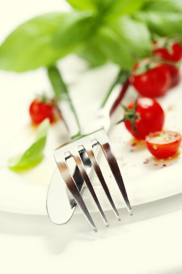 Tomates, couteau et fourchette frais d'une plaque images stock