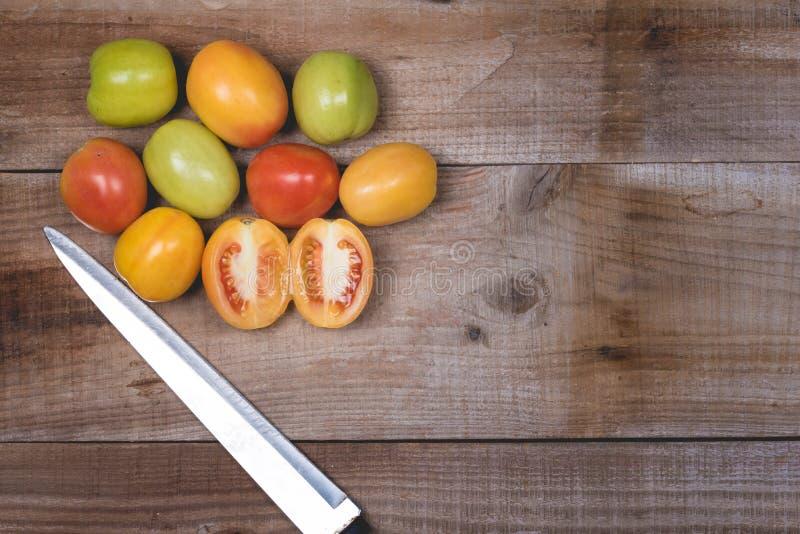 Tomates crudos en un fondo de madera imágenes de archivo libres de regalías