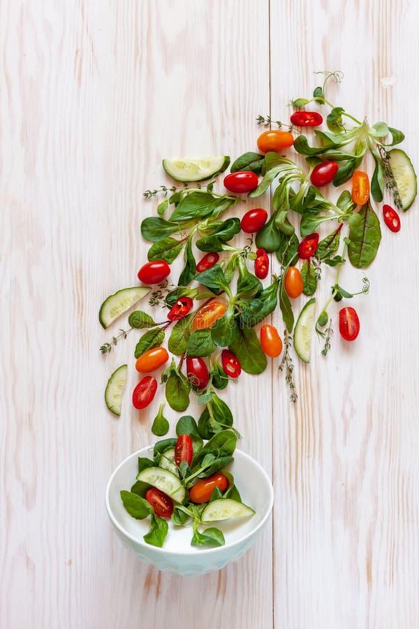 Tomates crudos frescos, pepinos, espinaca del bebé y verdes estacionales Visi?n superior, primer en el fondo de madera blanco imagen de archivo