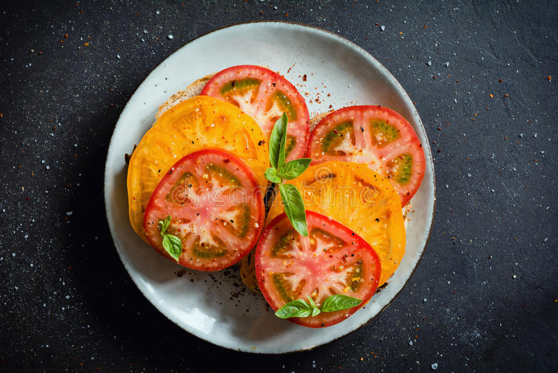 Tomates d'héritage avec le basilic et l'huile d'olive photographie stock libre de droits