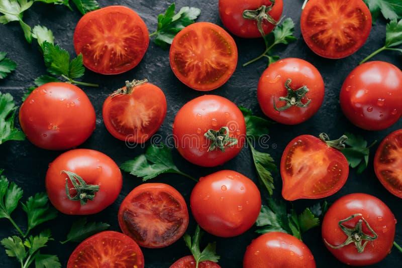 Tomates d'héritage avec le persil vert pour faire la salade végétale Légumes juteux sur le fond foncé Moisson et vitamines de nou photos stock