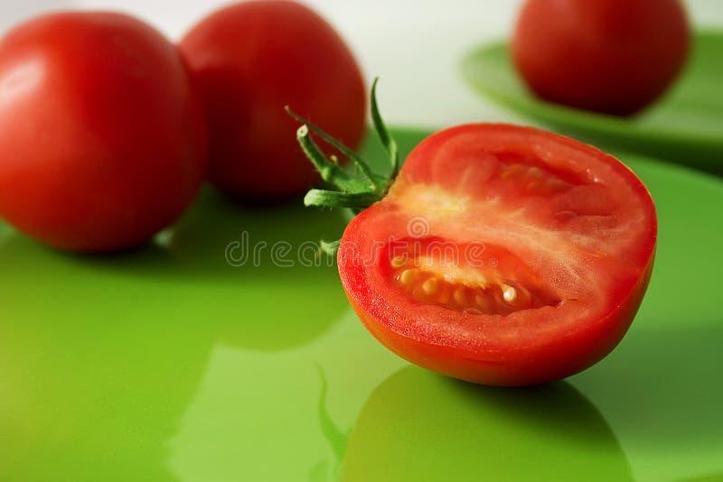 Tomates d'une plaque verte image stock