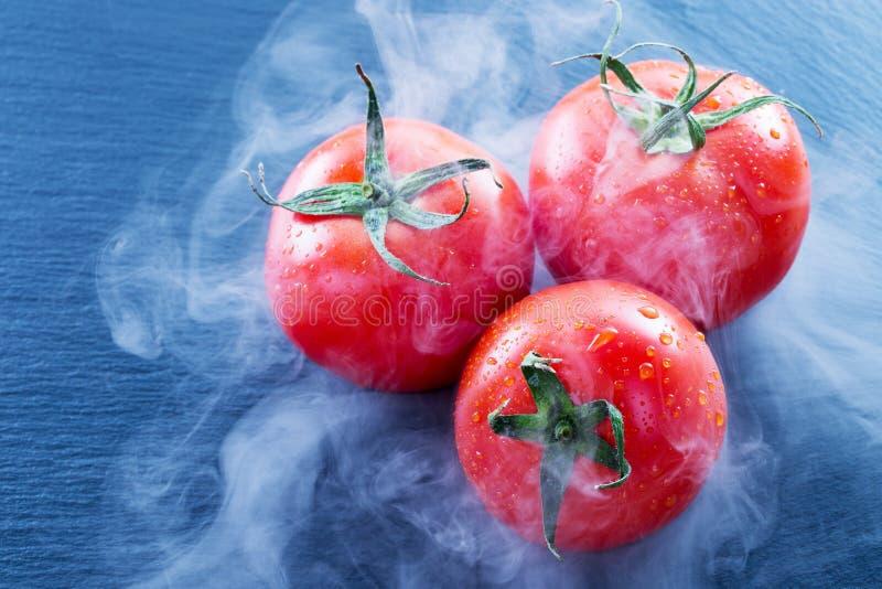 Tomates dans la fumée sur une table d'ardoise photos stock