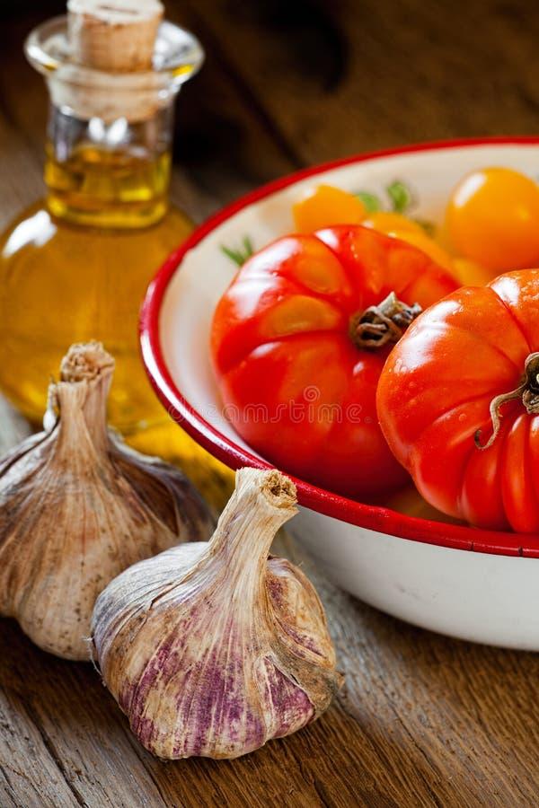 Tomates dans une cuvette, un ail et une huile d'olive photographie stock libre de droits
