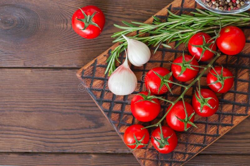 Tomates de cereja crus frescos em uma placa de madeira com alho a da pimenta imagem de stock royalty free