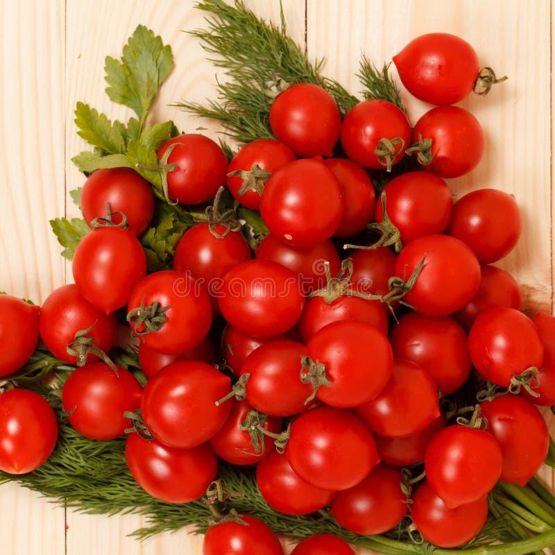 Tomates de cereja e ervas frescas no fundo de madeira foto de stock