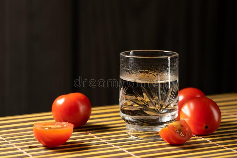 Tomates de cereja e vodca no estilo da casa da esteira foto de stock