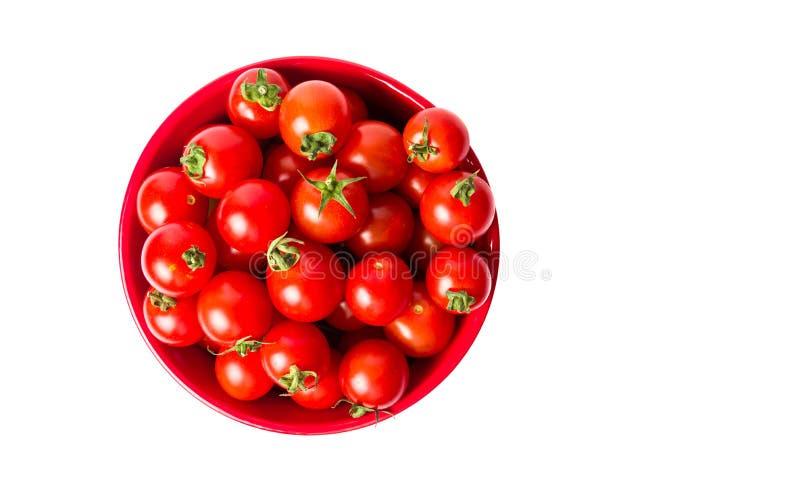 Tomates de cereja em uma bacia isolada imagens de stock