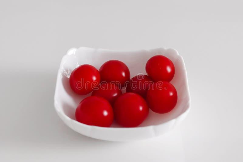 Tomates de cereja em uma placa branca fotografia de stock royalty free