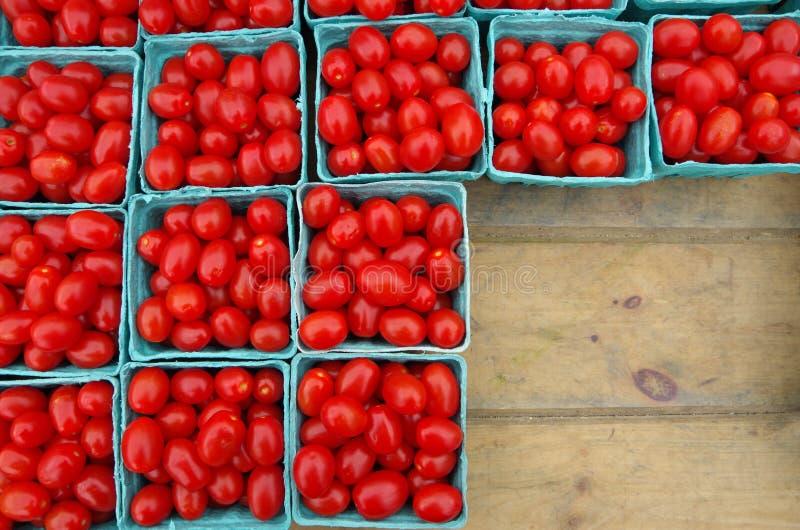 Tomates de cereja em uns recipientes azuis na tabela de madeira foto de stock